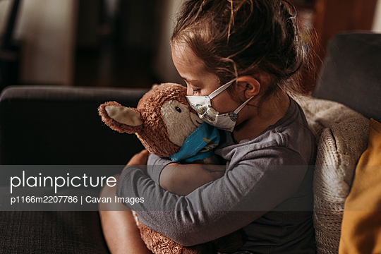 Close up of young girl with mask on kissing masked stuffed animal - p1166m2207786 by Cavan Images