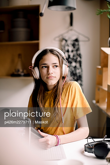 Girl wearing headphones sitting at desk while looking away - p426m2279711 by Maskot
