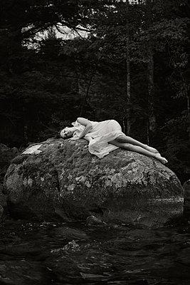 Junge Frau liegt auf einem Felsen - p1503m2031848 von Deb Schwedhelm