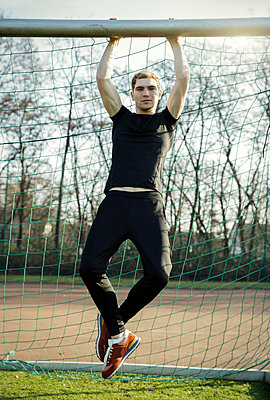 Young man doing chin-ups on football ground - p300m1029009f by Gabi Dilly