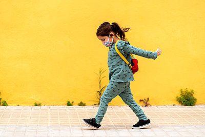 girl walking with backpack and mask outdoors - p300m2198088 by Ezequiel Giménez
