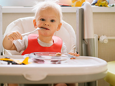 Cute little baby biting fork while sitting on high chair in kitchen - p300m2206830 by Konstantin Trubavin