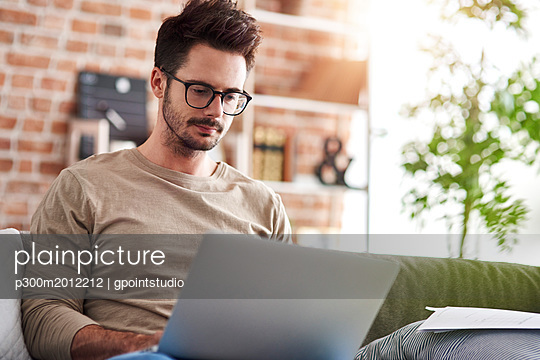 Portrait of man sitting on couch at home using laptop - p300m2012212 von gpointstudio