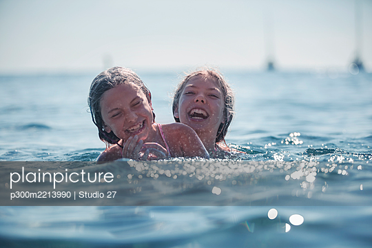 Girls playing in sea during summer - p300m2213990 by Studio 27