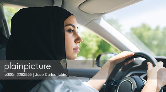 Woman in hijab looking away while driving car - p300m2293555 by Jose Carlos Ichiro