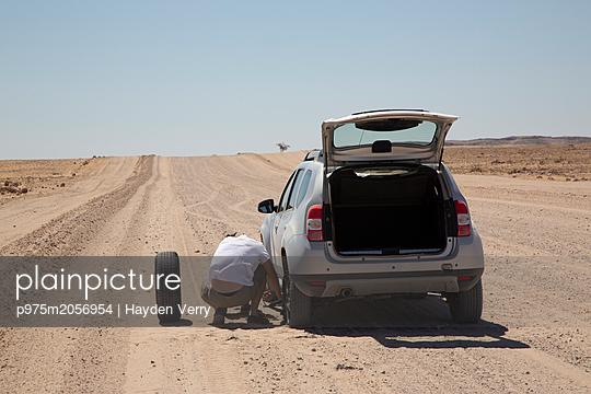 Man repariert ein Auto in der Wüste - p975m2056954 von Hayden Verry