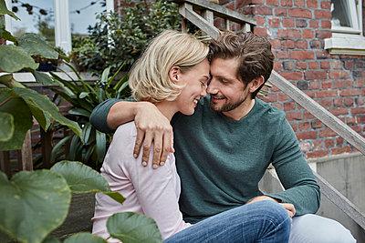 Happy couple sitting on stairs cuddling - p300m2081198 von Roger Richter