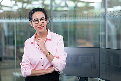 Smiling businesswoman standing by computers against glass wall at office - p300m2265188 by Florian Küttler