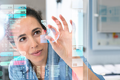 Female entrepreneur touching projection glass screen in factory - p300m2265199 by Florian Küttler