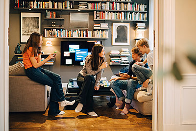 Friends talking and using mobile phone while sitting in living room at home - p426m1555865 by Maskot