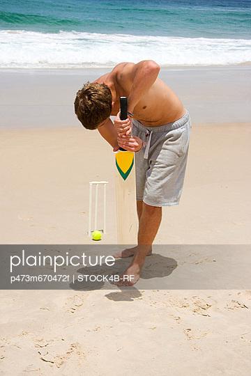 Junger Mann spielt Kricket am Strand