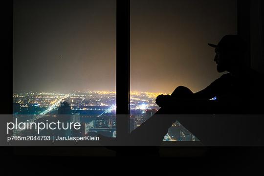 Mann sitzt auf Fensterbank und blickt auf die Skyline von Kaohsiung - p795m2044793 von Janklein