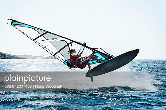 Young man windsurfing above ocean waves, Limnos, Khios, Greece - p924m2097450 by Ross Woodhall