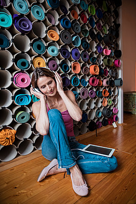 Relaxed mature woman listening to music in front of assortment of yoga mats - p300m1562651 by Robijn Page