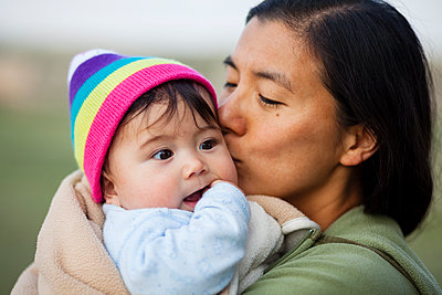 Portrait of woman kissing baby girl - p343m1446651 by Steve Glass