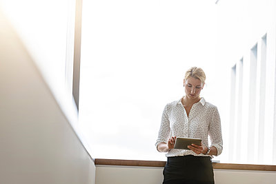 Businesswoman using digital tablet at corridor - p429m2091692 by suedhang photography