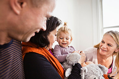 Grandmother holding toddler granddaughter with parents - p429m803487f by Christoffer Askman
