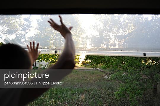 Jugendlicher blickt aus dem Fenster im Wohnwagen - p1468m1584995 von Philippe Leroux