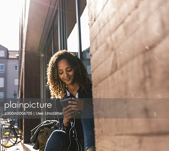 Young woman sitting in front of window in the city, using smartphone - p300m2004705 von Uwe Umstätter