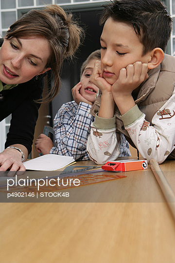 A Teacher drawing on a Desk with two Pupils - Lesson - Education