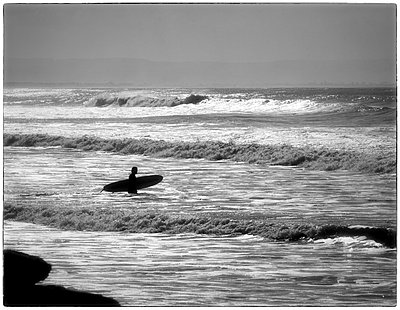 Surfer walking in surf - p1154m1110189 by Tom Hogan