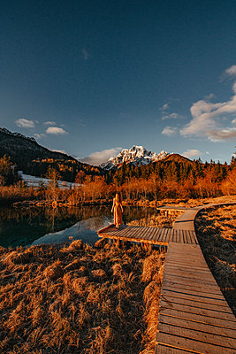 Woman enjoys a early morning sunrise at the Zelenci Natural Reserve in Slovenia - p1455m2081763 by Ingmar Wein