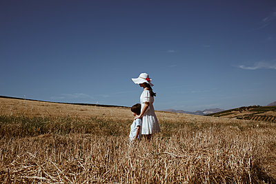 A girl and a child in a field - p1623m2289592 by Donatella Loi