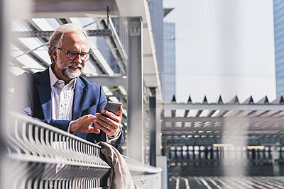 Smiling mature businessman in the city using cell phone - p300m1587883 von Uwe Umstätter