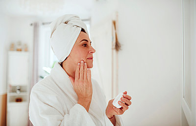 Mature woman in a bathroom at home applying moisturizer - p300m2103217 by HalfPoint