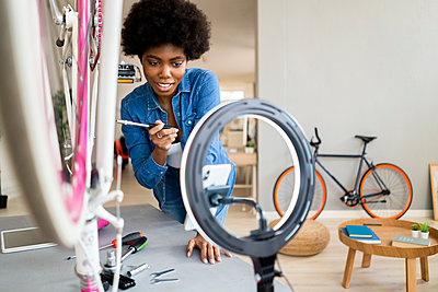 Smiling female influencer using mobile phone while repairing bicycle at home - p300m2275890 by Giorgio Fochesato