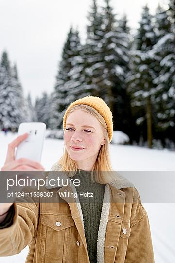 Junge Frau macht ein Selfie im Schnee - p1124m1589307 von Willing-Holtz