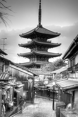 Street lined with traditional buildings with tall wooden pagoda of Buddhist temple in distance. - p1100m1570882 by Mint Images