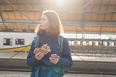 Woman using mobile phone while having wrap food in railway station - p1315m1566477 by Wavebreak