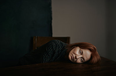 Exhausted and depressed woman laying on the desk - p1577m2217437 by zhenikeyev
