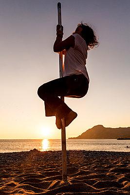 Girl climbing up pole on sandy beach in Crete - p1687m2295107 by Katja Kircher