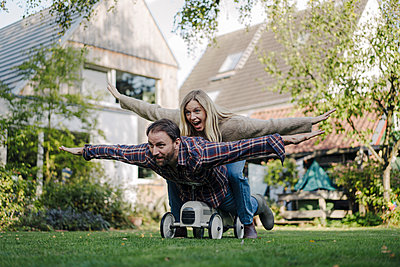 Laughing couple, pretending to fly on a toy car in the garden - p300m2166729 by Kniel Synnatzschke