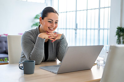 Smiling businesswoman on video conference call using laptop while working at home - p300m2274601 by Giorgio Fochesato