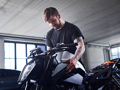 Technician checking motorcycle part at repair shop - p300m2281557 by Christian Vorhofer