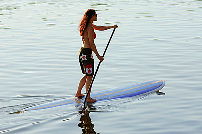 Mid adult woman stand up paddle surfing - p31227565f by Hans Berggren