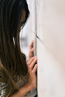 Woman touching wooden wall with hand - p586m1020381 by Kniel Synnatzschke