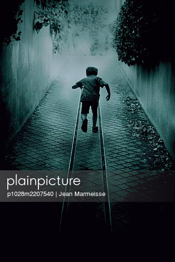 Boy running away - p1028m2207540 by Jean Marmeisse
