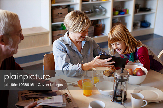 Man looking at wife showing tablet computer to granddaughter while sitting at table - p1166m1038616f by Cavan Images