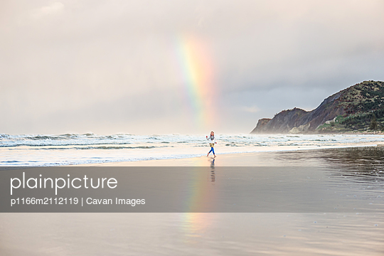 Girl running on a beach under a rainbow near a mountain - p1166m2112119 by Cavan Images