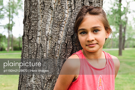 Portrait of young girl leaning against tree and looking at camera - p1192m2129870 by Hero Images