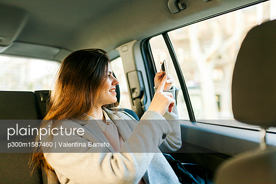 Smiling young woman sitting on backseat of a car taking picture with cell phone - p300m1587460 von Valentina Barreto