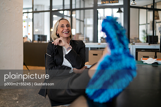 Laughing mature businesswoman with feet on desk wearing cleansing slippers in office - p300m2155245 by Gustafsson