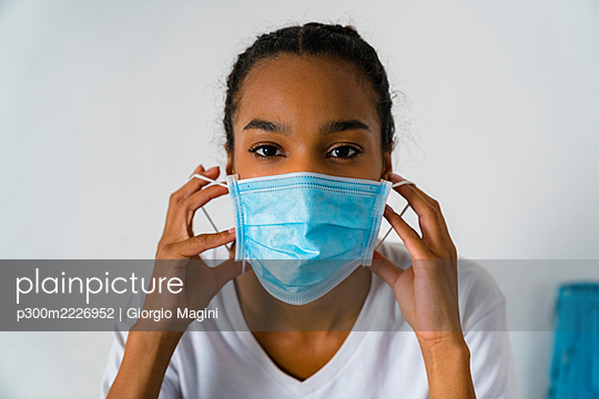 Young girl wearing protective face mask standing against wall - p300m2226952 by Giorgio Magini