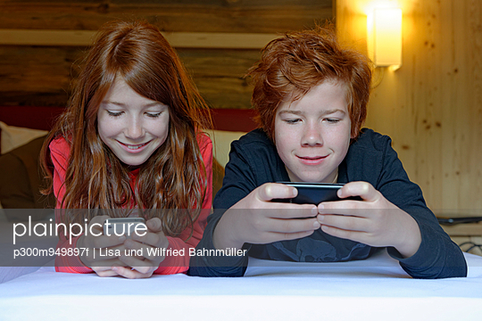 Portrait of brother and sister lying on bed using their smartphones - p300m949897f by Lisa und Wilfried Bahnmüller