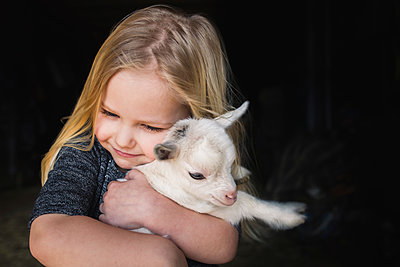 High angle view of girl embracing kid goat - p1166m1524992 by Cavan Images