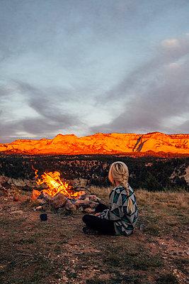 Woman sitting by bonfire against mountains - p1166m1544605 by Cavan Social
